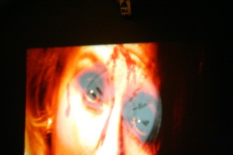 Close up of a woman's face projected in orange hues on a wall