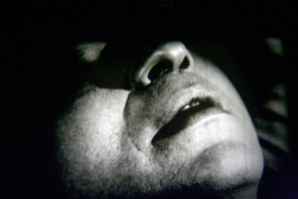 The jaw, mouth and nose of a man's face, the rest in shadow