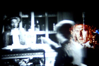 Black and white projections with a wigged man appearing in colour on the right