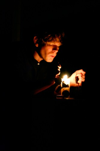 Joe Colley's face lit by a candle his hand holding an electrode nearby