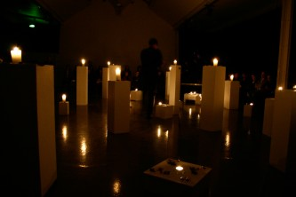 A room full of plinths with candles on top
