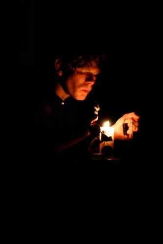 Joe Colley's face lit by a candle his hand holding an diode nearby