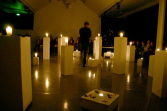 A room full of plinths with candles on top, audience nearby