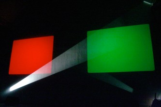 Rectangles of red and green behind a beam of white light