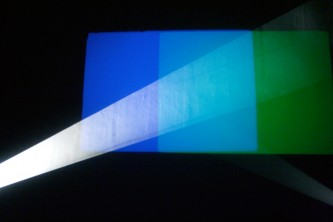Rectangles of blue, pale blue and green in front of a beam of white light