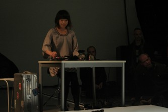 Sachiko M operating a sampler at a table