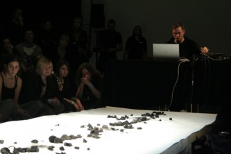 Benedict Drew operating a mixer at the end of a strip of paper with charcoal