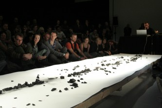 A long sheet of paper before an audience, charcoal on top