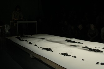 A long sheet of paper with charcoal on top