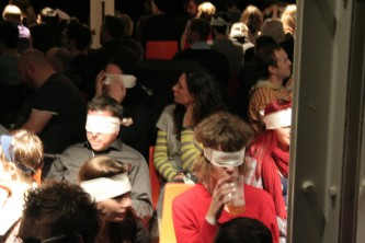 An audience seated and wearing eye masks, someone drinking beer