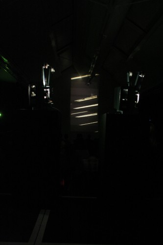 Two projectors glowing in darkness