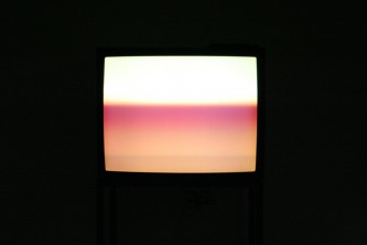 A cathode ray tube television showing bands of pink light