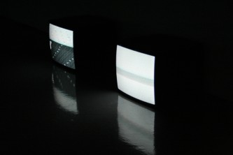 Two tv monitors  in a gallery showing patterns of dots