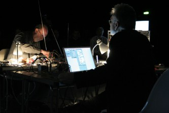 Keith Rowe and Kjell Björgeengen working among screens and devices