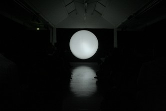A white circle of light at the far end of a long room
