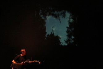 Lee Patterson sitting next to a projection of trees