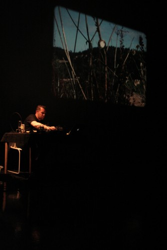 Lee Patterson sitting next to a projection of a contact mic on a bush