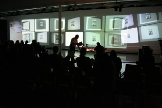 A long screen with images projected onto it before an audience