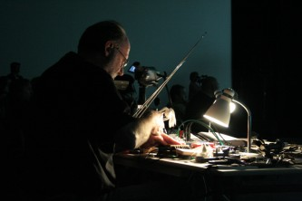 Keith Rowe playing a table top guitar under lamplight