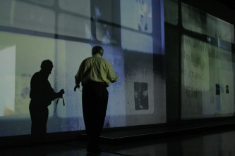 Malcolm Le Grice Silhouetted against a long screen showing fragmented images