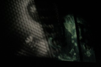 Gauze and emerald green forms projected on a screen