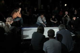 An audience seated around a pool of water with projections on its surface