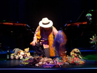 Charlemagne Palestine seated at two pianos surrounded by soft toys