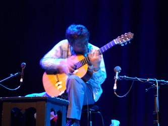 Kazuo Imai's fingers blurred with movement while playing an acoustic guitar