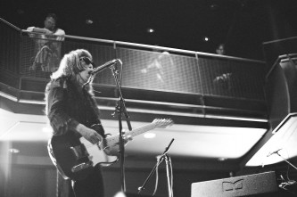 Keiji Haino playing a fender telecaster guitar and singing into a microphone