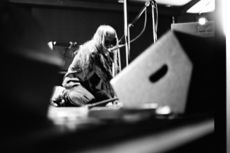 Keiji Haino kneeling down near monitor speakers singing into a microphone