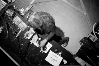 Keiji Haino performing next to a sign saying 'Danger Unstable Load'