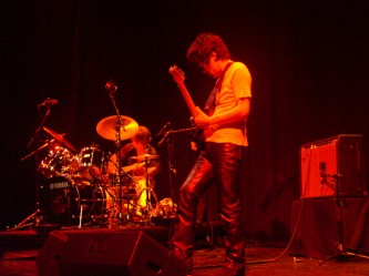 Kyoaku No Intention on stage playing drums and guitar in orange light at MLFC 05