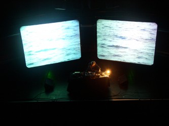 Takehisa Kosugi operating electronic devices near projector screens