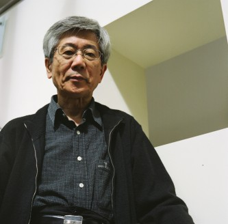 Takehisa Kosugi in dark clothes smiles down at the camera in a white stairwell