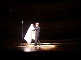Takehisa Kosugo comes onstage carrying a sheet of paper towards a microphone