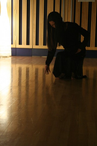 Butoh dancer dressed in black poised on a wooden floor lit from the side