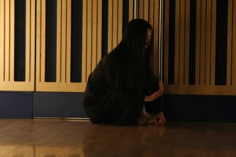 Yoko Muronoi sitting by a wall during a dance performance at MLFC