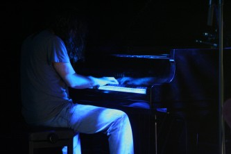 John Blum playing the piano in low level lighting at MLFC 07