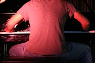 The back of John Blum while he plays the piano