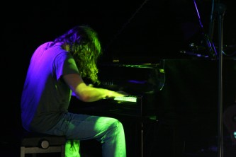 John Blum seated at a piano in blue and green light at MLFC 07