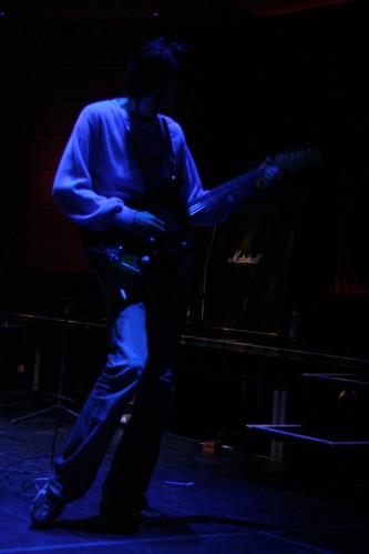 A man in a cardigan playing a guitar in dim blue light
