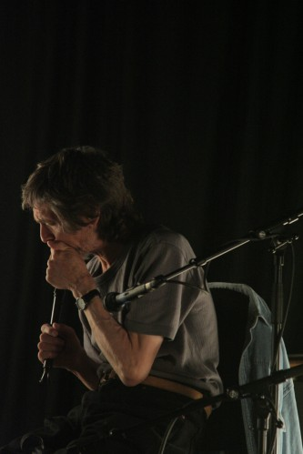 A seated Terry Day blowing a recorder