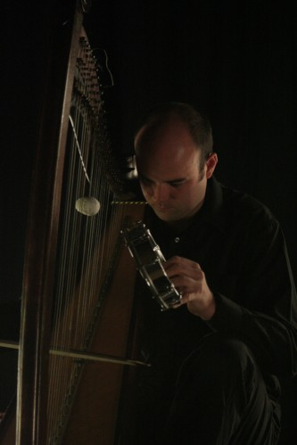 Rhodri Davies bowing a harp with a small hand drum held against the strings
