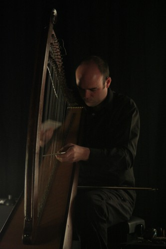 Rhodri Davies inserting an object between the strings of a harp