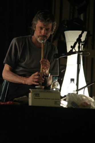 Terry Day blowing a reed instrument perched on a box