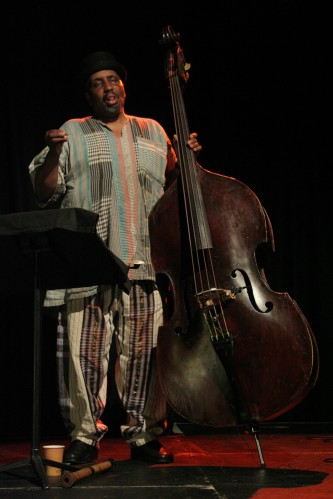 William Parker standing in concentration next to a double bass