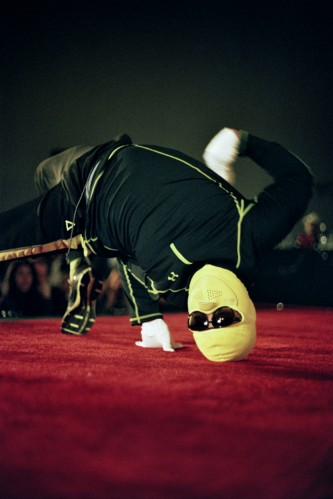 upside down figure in lemon yellow ski mask and sunglasses on a red carpet