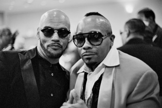 Two men in fabulous shades and evening wear smile at the camera