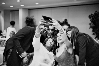 A group of people in evening wear group together for a selfie