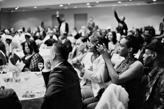 A large crowd wearing evening wear are sat at tables applauding